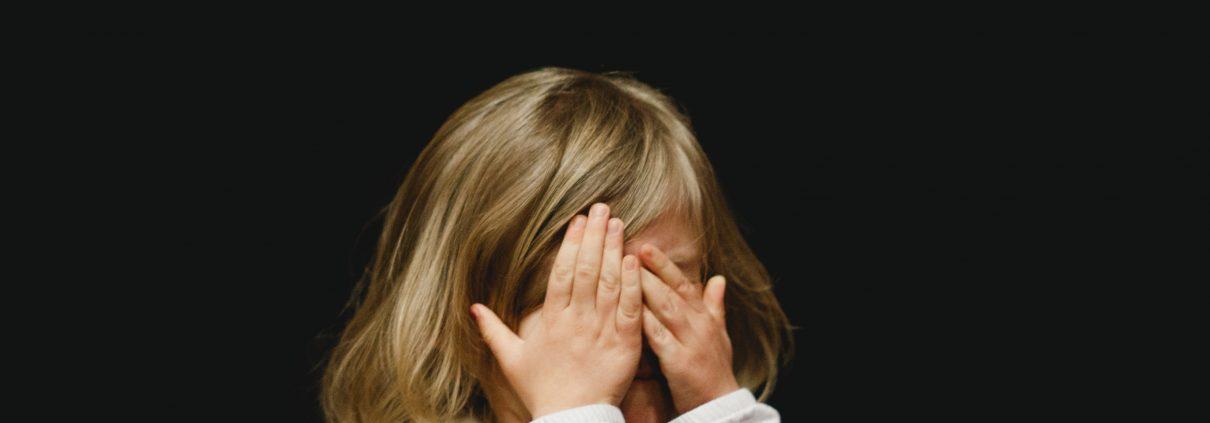 Little girl covering her face
