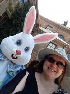 Headshot of Paula McMahon. She's wearing sunglasses and a sun hat and is standing next to a person in a bunny costume.