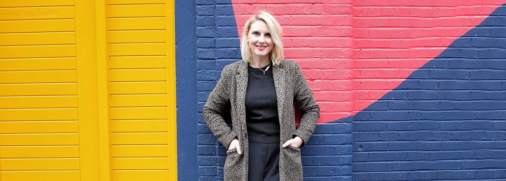 Photo of Victoria Clapham standing against a brightly coloured wall. She has her hands in her coat pockets and is smiling.